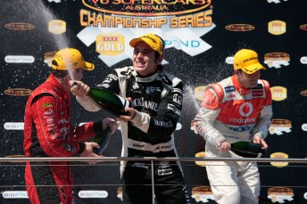 Rick Kelly celebrates his second place on the Island podium with Garth Tander and Jamie Whincup