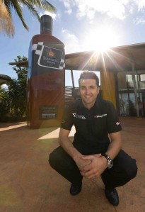 Fabian Coulthard stands in front of a very large bottle of Bundy Racing rum