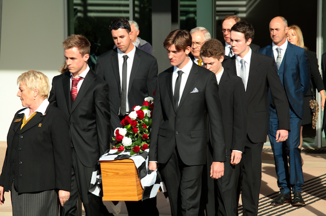 Sir Jack Brbaham's grandsons Matthew and Sam lead the casket out of the church